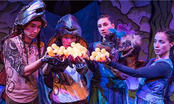 Four dancers stand in a row. They wear blue and purple costuming, the two of the left their costumes are hooded. They hold a bunch of bright yellow spheres in their hands together and stare at them with awe.