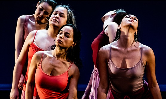 Five dancers are seen from their waist up. They wear orange and mauve tank tops. They vulnerably press their chest and neck forward with eyes closed.