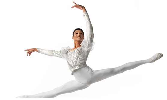 Vladimir is captured in the height of a jété. He wears white tights, shoes and a ornate long sleeve shirt. He smiles broadly as he looks under his raised arms.