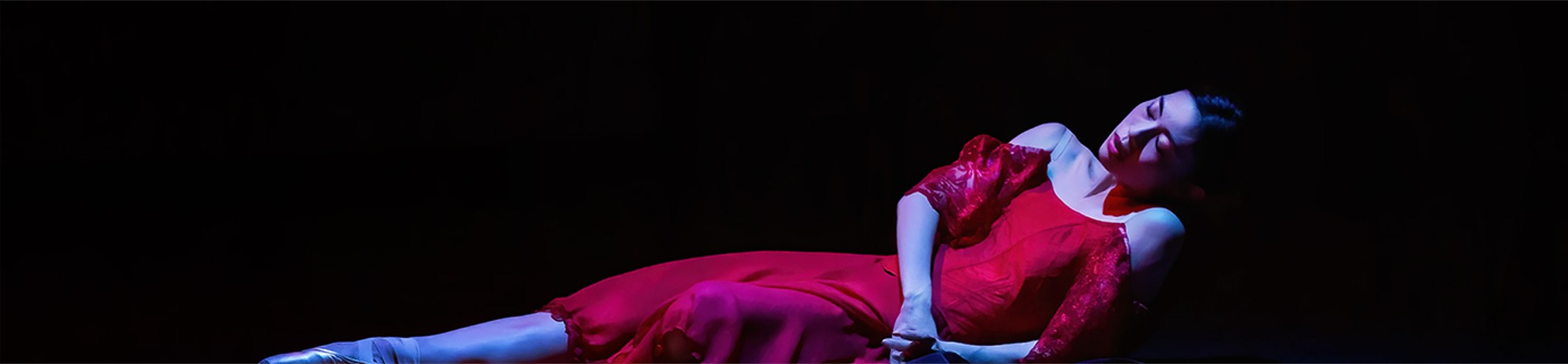 A woman lies down propped up on her elbow. She softly lays in a red dress wearing pointe shoes.