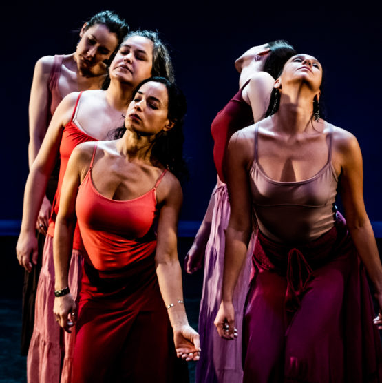 Five dancers are close together and softly press their neck and chest forward with closed eyes. They wear tank tops and skirts in varying shades of orange, red and burgundy.