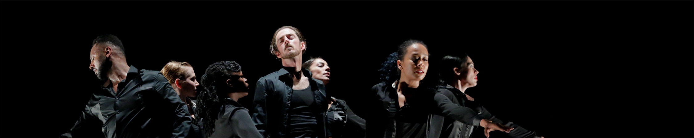 Several dancers stand in all black in varying directions. They reach and lean outwards from the centre grouping.