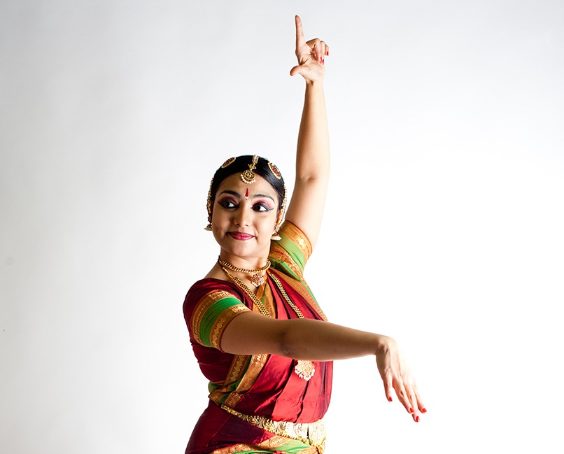 Arno stands with one arm extended overhead and three fingers coming into the fist with the first and thumb extended. The other arms points forward from her shoulder and folds at the wrist. She stands in front of a white background in a ornate red sari with gold and green edging.