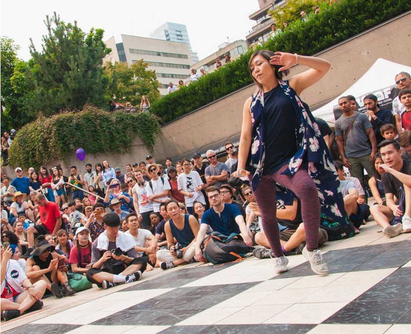 Ikue is in a pose with one heel popped. She leans to that side with the arm folded to her face. She dances on an outdoor black and white checkered area with a large surrounding crowd seen behind her.