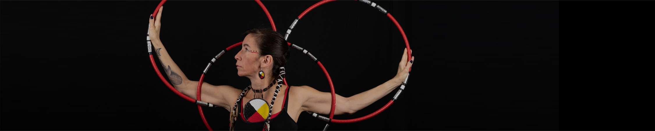 Barbara faces profile and spreads her arms out wide between three hoops, forming overlapping shapes. The hoops are red with white, silver and black details. She wears layered black and red tank tops with a large necklace with the four realms image (black, red, white and yellow quarters).